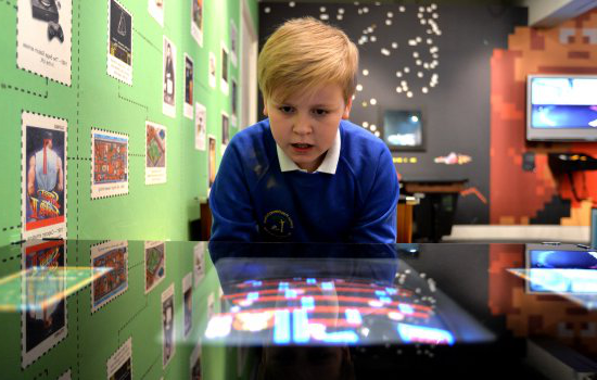 A child looking at a console in the Games Lounge gallery