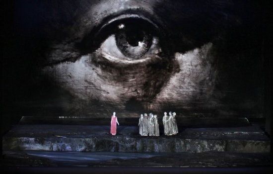 A stage view of the backdrop for Der Fliegende Hollander, showing a large illustration of an eye overlooking a group of small figures