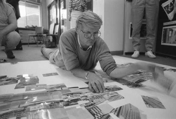 A black 和 white photography of David Hockney lying on the floor looking at images