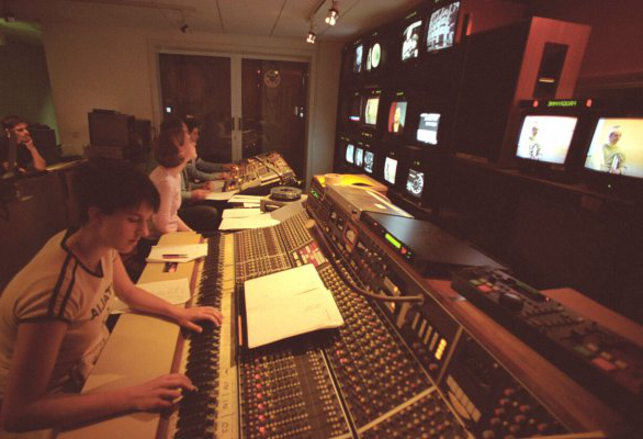 A photograph of people sitting in front of mixing desk