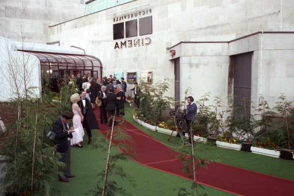 A photograph of a red carpet leading up to a white building