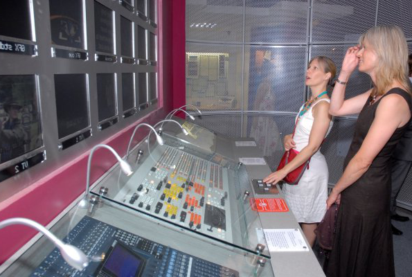 A photograph of two women looking at a mixing desk exhibit in the Museum