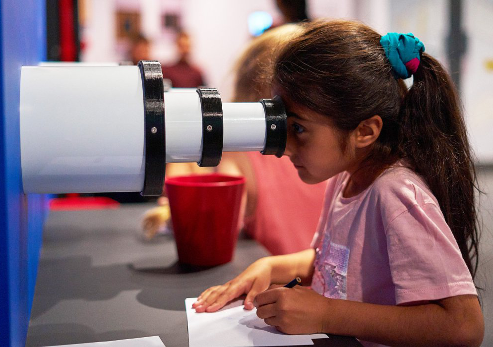 A girl looks through the eye of a telescope