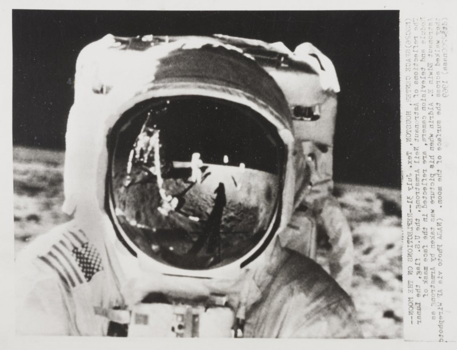 The reflections of Astronaut Neil Armstrong, the US flag, the Lunar Module and telev是ion camera, are reflected in the face mask of Astronaut Edwin E Aldrin when the picture was taken by Armstrong as they walked a交叉 the surface of the moon