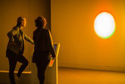 Image shows two visitors looking at an exhibit in a gallery space