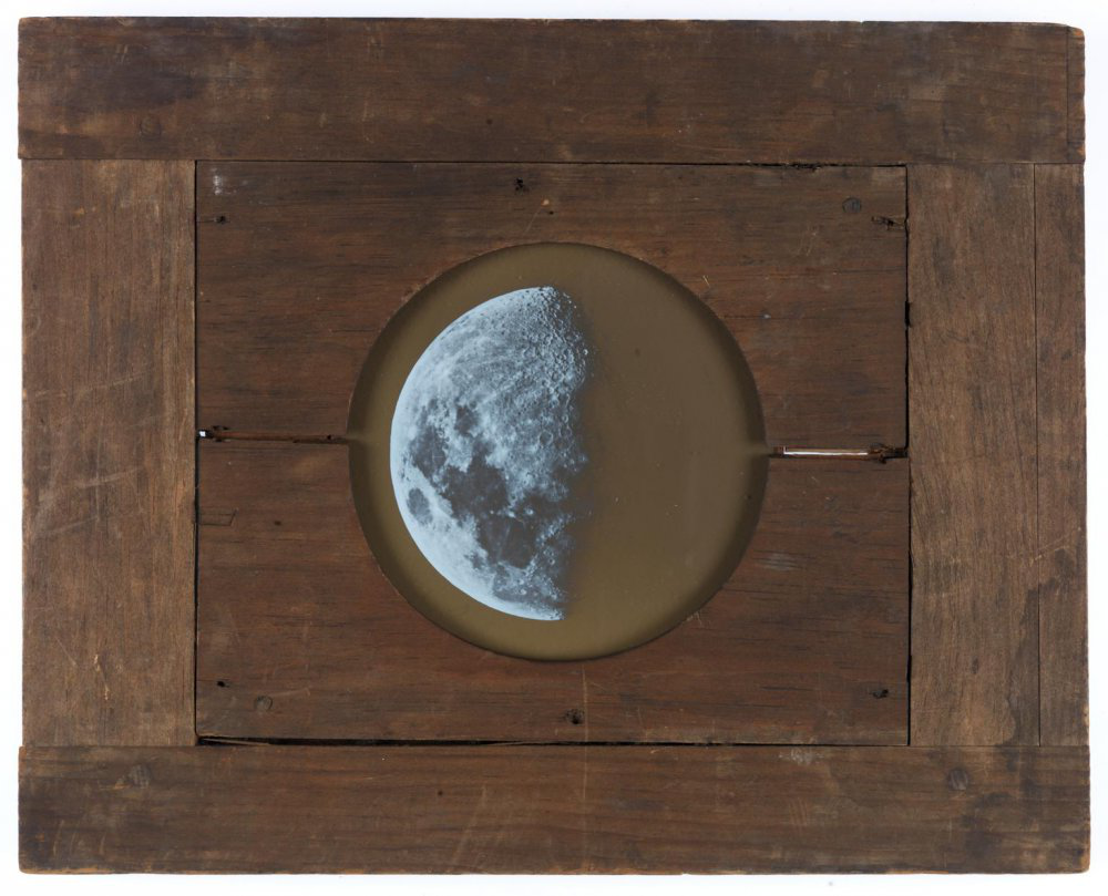 Magic lantern slide show在g the Moon. A circular illustration of the Moon is shown at the centre of a wooden board