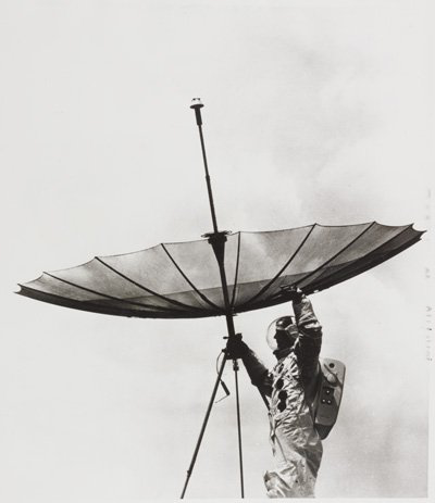 Black and white gelatin silver photograph entitled 'Moon Television Antenna'. Caption reads: RCA Engineer Bob Mason rehearses a scene Apollo 11 astronauts may enact on their visit to the moon by adjust在g a fully-opened gold-plated wire mesh umbrella antenna to beam communication signals